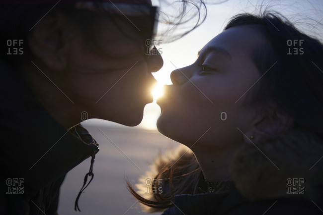 Optical illusion of sisters kissing sun at beach during sunset