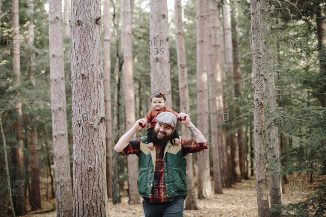 Happy father carrying daughter on shoulders while walking in forest