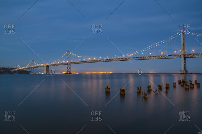 Illuminated Oakland Bay Bridge against blue sky at dusk