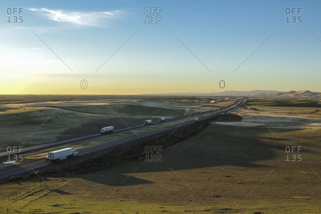 High angle view of trucks on country road against blue sky