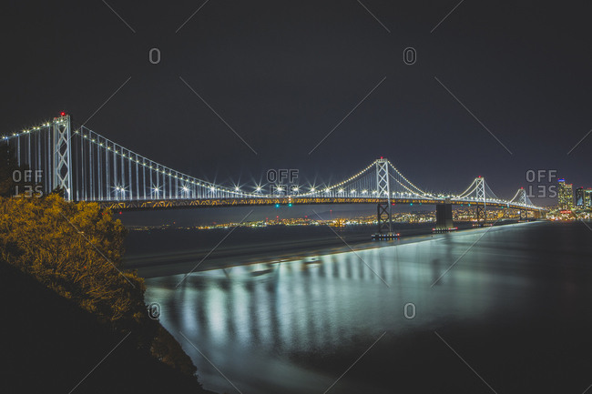 Illuminated Oakland Bay Bridge against clear sky at night