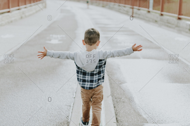 Rear view of boy with arms outstretched walking on street