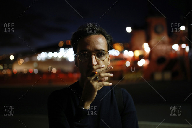 Portrait of man smoking while standing on street at night
