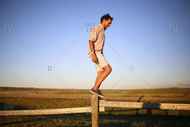 Full length of happy man balancing on wooden fence against clear blue sky during sunset
