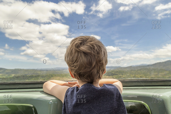 Boy looking through rear windshield while traveling in car