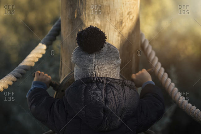 Rear view of boy in warm clothing spinning steering wheel at playground