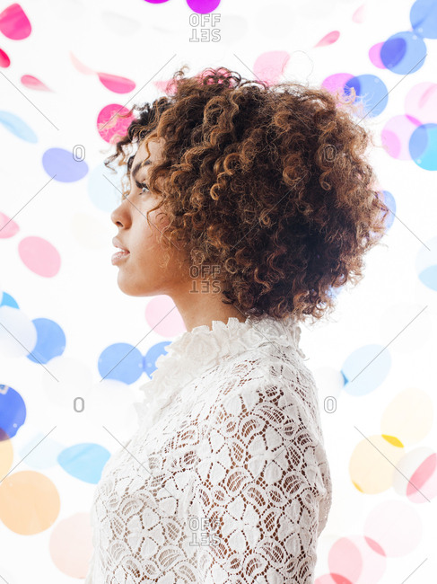 Side view of woman by multi colored decoration against white background