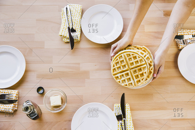 Overhead view of woman holding waffles in plate at table