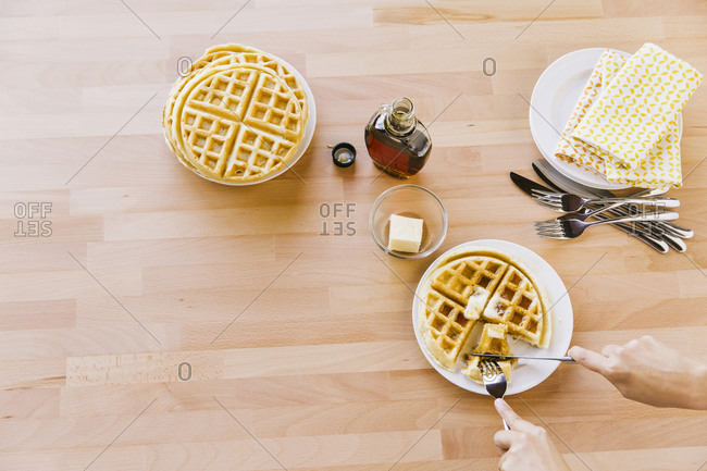 Overhead view of woman eating waffle at table