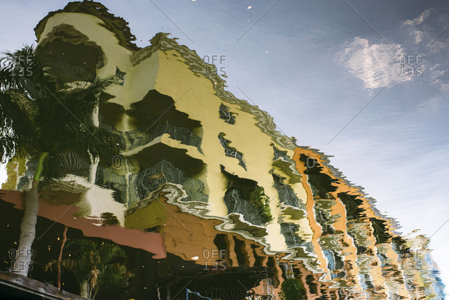 Reflection of apartment building and palm tree in a river in Fort Lauderdale