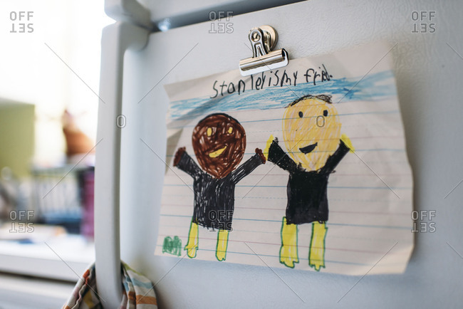 Child's drawing of African American and Caucasian friends hung on a refrigerator with a magnet
