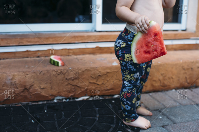 Midline view of toddler girl eating messy watermelon without a shirt