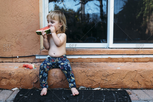 Toddler girl eating messy watermelon without a shirt outside