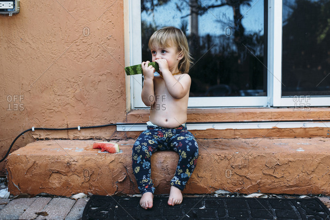 Toddler girl sitting on step eating messy watermelon