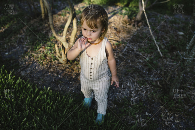 Toddler in striped romper standing in a patch of light in a park