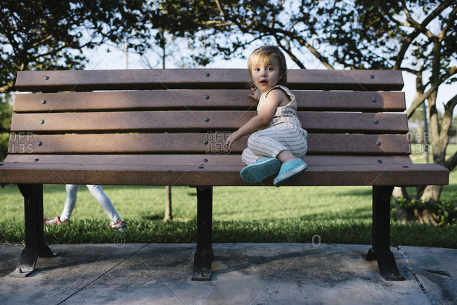 Toddler in striped romper sitting on park bench