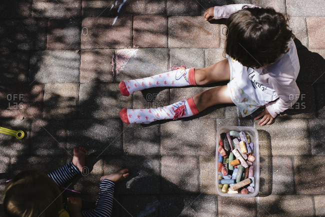 Sisters coloring with sidewalk chalk on patio, shot from above