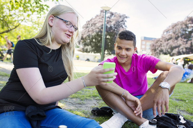 Teenage girl and teenage boy (14-15) looking at smart phone in park