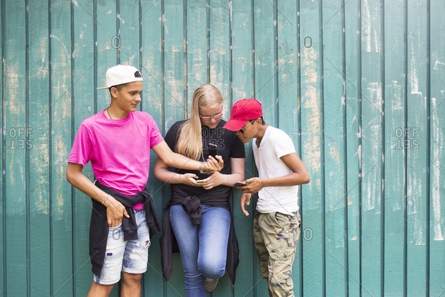 Teenage girl and teenage boys (14-15) looking at smart phone