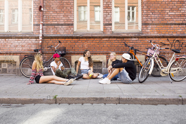 Teenage girls and teenage boys (14-15) sitting on sidewalk