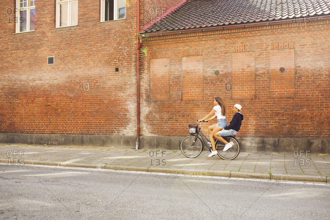 Teenage girl and teenage boy (14-15) riding bicycle together
