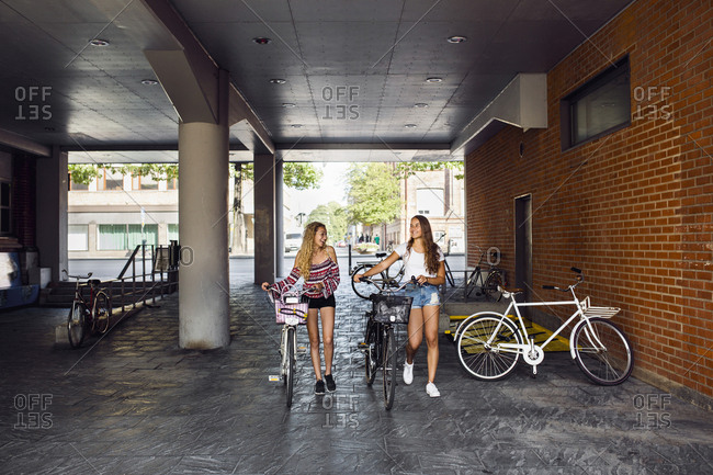 Two teenage girls (14-15) walking with bicycles