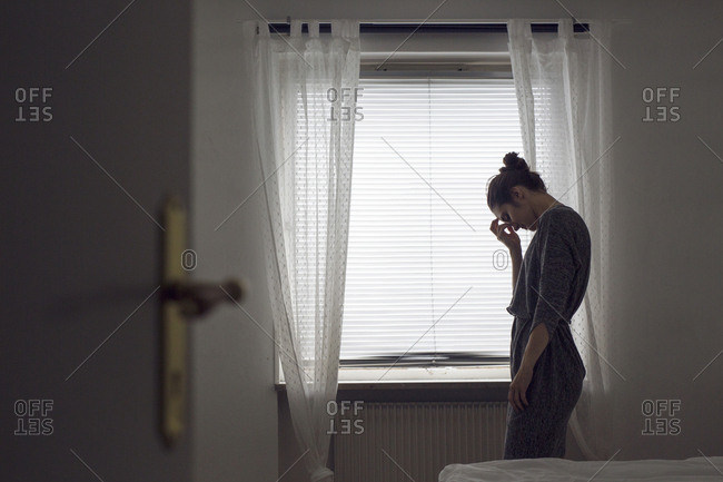 Pensive young woman standing by window