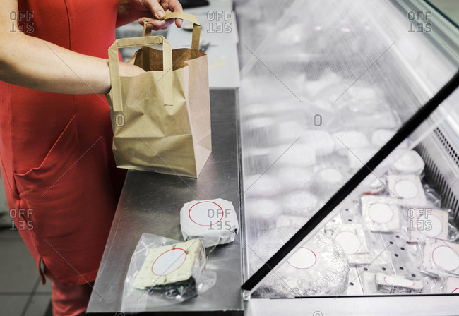Sales clerk packing cheese into paper bag
