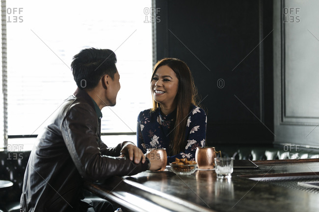 Couple sitting at bar counter in brightly lit restaurant