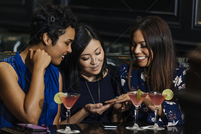 Happy woman showing nail polish to female friends while sitting at table in bar