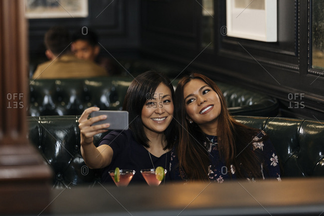 Female friends taking selfie with smart phone while sitting in bar