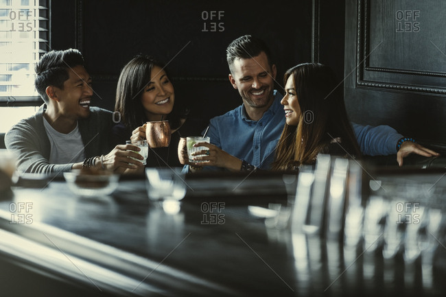 Happy multiethnic couples toasting drinks while sitting in restaurant