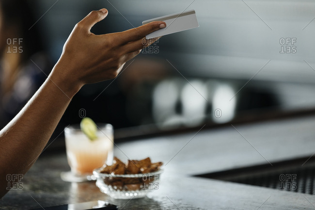 Cropped image of woman's hand holding credit card at bar counter in restaurant