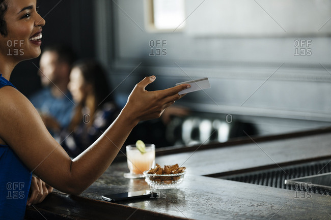 Happy woman holding credit card while sitting at bar counter in restaurant