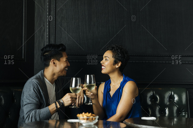 Happy couple toasting with wine glasses in bar