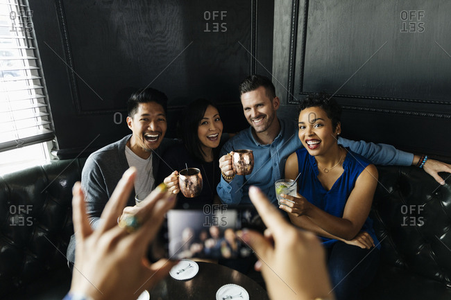 Cropped image of woman photographing group of friends holding drinks in bar