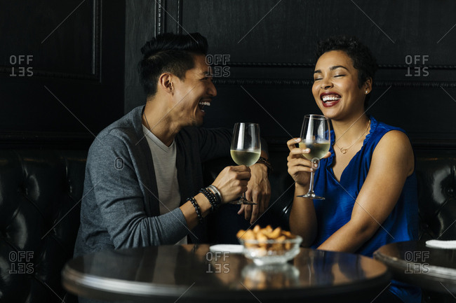Happy couple holding wineglasses while sitting in bar at restaurant