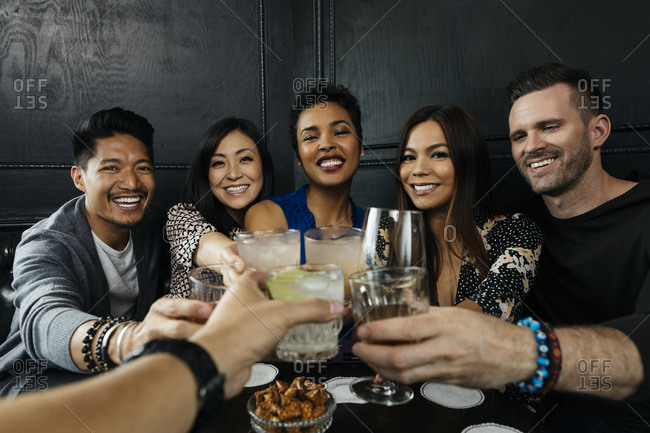 Group of happy multiethnic friends toasting drinks at bar in restaurant