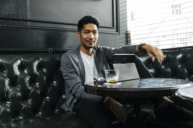 Portrait of handsome man sitting on black couch in brightly lit bar