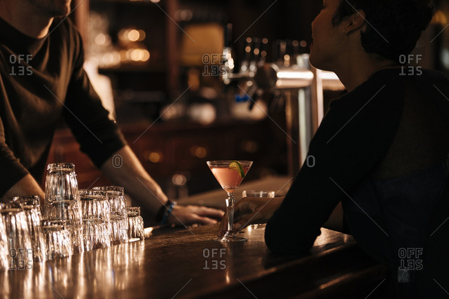 Woman looking at bartender while sitting at bar counter in restaurant