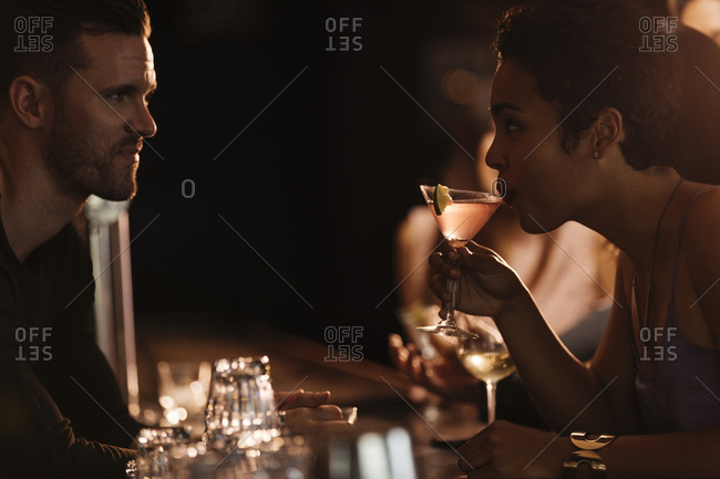 Side view of woman looking at bartender while drinking cocktail from martini glass in nightclub