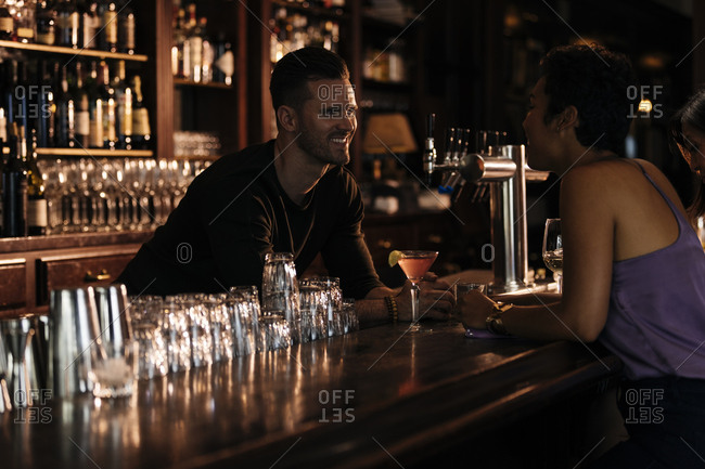 Happy male bartender talking to female customer at bar