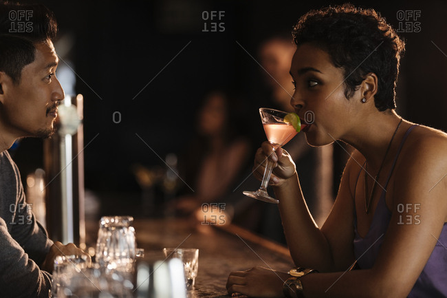 Woman looking at bartender while drinking cocktail from martini glass in nightclub