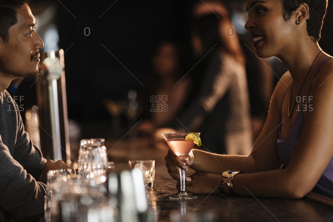 Happy woman talking to male bartender at bar counter in nightclub