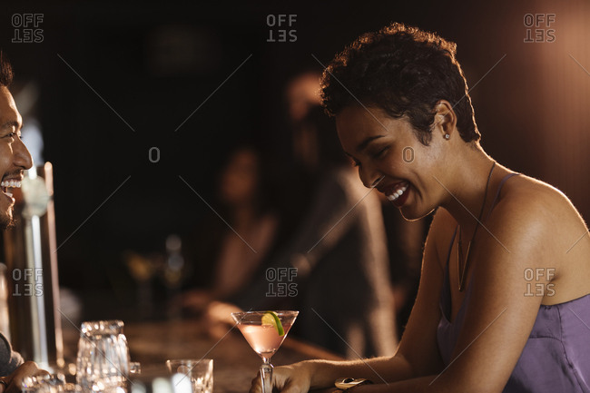 Cheerful woman with bartender at bar counter in nightclub