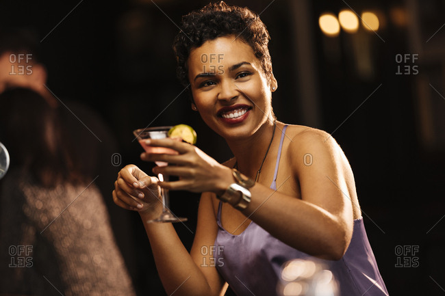 Portrait of happy woman holding martini glass while sitting in bar at restaurant