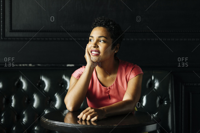 Smiling woman looking away while sitting with hand on chin at table in bar