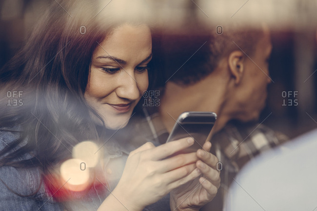 Woman looking at smart phone in bar