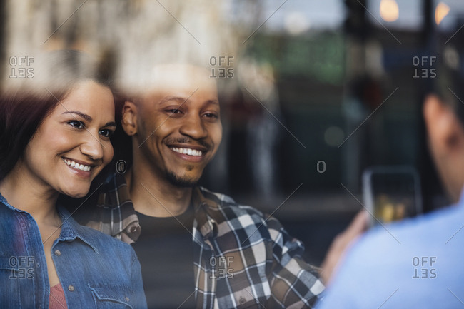 Multiethnic man and woman pose for friend taking a photograph in bar