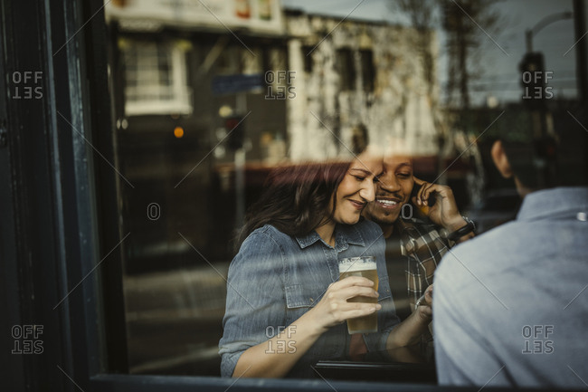 Happy woman holding beer glass by friend seen through bar window